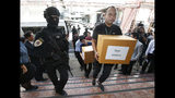 Thai policemen guard next to 100 kilograms of seized marijuana before a news conference Bangkok, Thailand, Tuesday, Sept. 25, 2018. Thai police handed over around 100 kilograms of seized marijuana to be used for medical research Tuesday, as officials seek to produce pot-based medication. (AP Photo/Sakchai Lalit)