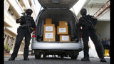 Thai policemen stand guard next to 100 kilograms of seized marijuana before a news conference Bangkok, Thailand, Tuesday, Sept. 25, 2018. Thai police handed over around 100 kilograms of seized marijuana to be used for medical research Tuesday, as officials seek to produce pot-based medication. (AP Photo/Sakchai Lalit)