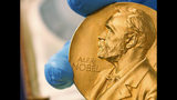 FILE- In this April 17, 2015, file photo a national library employee shows the gold Nobel Prize medal awarded to the late novelist Gabriel Garcia Marquez, in Bogota, Colombia. This year's round of Nobel Prizes begins Monday, Oct. 1, 2018, with the award for medicine or physiology, honoring research into the microscopic mechanisms of life and ways to fend off the invaders who cut it short. (AP Photo/Fernando Vergara, File)