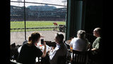 Patrons inside the Bleacher Bar enjoy the view of Fenway Park, in Boston, Wednesday, Oct. 10, 2018, as grounds crew get the field ready for Game 1 of the baseball American League Championship Series between the Boston Red Sox and the Houston Astros. The game is scheduled for Saturday, Oct. 13, 2018. (AP Photo/Elise Amendola)