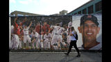 A woman walks by large photo scrims hanging outside Fenway Park showing Boston Red Sox players and manager Alex Cora, Wednesday, Oct. 10, 2018, in Boston. Game 1 of the baseball American League Championship Series between the Red Sox and the Houston Astros is scheduled for Saturday in Boston. (AP Photo/Elise Amendola)
