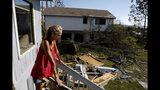 """Monica Jones looks out over the debris littering her yard after riding out hurricane Michael in her home in Callaway, Fla., Thursday, Oct. 11, 2018. """"I didn't think it was going to be this bad,"""" said Jones on her decision to stay through the storm. The devastation inflicted by Hurricane Michael came into focus Thursday with rows upon rows of homes found smashed to pieces, and rescue crews began making their way into the stricken areas in hopes of accounting for hundreds of people who may have stayed behind. (AP Photo/David Goldman)"""