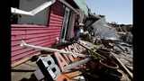 Matthew Washington carries out items he salvaged from the damaged Thai restaurant he owns with his wife in the aftermath of hurricane Michael in Callaway, Fla., Thursday, Oct. 11, 2018. (AP Photo/David Goldman)