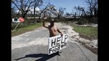 """Michael Williams, 70, waves to passing motorists while looking for food and water as downed trees prevent him from driving out of his damaged home with his family in the aftermath of Hurricane Michael in Springfield, Fla., Thursday, Oct. 11, 2018. """"I don't know what I'm going to,"""" said Williams. (AP Photo/David Goldman)"""
