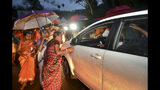 Hindu women favoring barring women of menstruating age from entering the Sabarimala temple scan vehicles at Nilackal, a base camp on way to the mountain shrine in Kerala, India, Tuesday, Oct. 16, 2018. The historic mountain shrine reopens Wednesday the first time after India's Supreme Court lifted the ban, holding that equality is supreme irrespective of age and gender. Devotees have been protesting against the verdict demanding that the customs and rituals of the temple should be protected. (AP Photo)