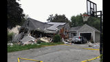 FILE - In this Thursday, Sept. 13, 2018 file photo, a collapsed home and car sit damaged on Chickering Street in Lawrence, Mass., after a series of gas explosions in several communities north of Boston. Authorities said Leonel Rondon died after the chimney toppled by the exploding house crashed into his car in the driveway. The family of Rondon, 18, plans to file a wrongful death lawsuit against Columbia Gas. (Carl Russo/The Eagle-Tribune via AP, File)