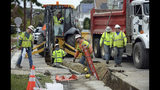 In this Monday, Oct. 8, 2018 photo, technicians work in a freshly cut trench, in Lawrence, Mass., as work continues to replace miles of gas lines that were damaged when dozens of gas explosions ripped through three Massachusetts communities in Sept. of 2018. The family of Leonel Rondon, 18, who was killed during the explosions, plans to file a wrongful death lawsuit against Columbia Gas. (Ryan Hutton, The Eagle-Tribune via AP)