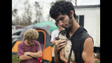 In this Oct. 23, 2018 photo, Ronald Lauricella cradles a kitten in his front yard in Bay County, Fla.,. The rural Bay County resident says some on the outskirts of the cities aren't getting needed services like electricity as fast as the populated areas. (AP Photo/Tamara Lush)