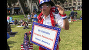 """Harvey Rosenfeld attends a Democratic party rally Saturday, Nov. 3, 2018, in West Palm Beach, Fla., bedecked in a red, white and blue outfit topped with an Uncle Sam hat and had a sign around his neck reading, """"Be Patriotic, Respect Democracy, Honor America."""" The 68-year-old retired publicist said he had been a Republican for 30 years until its stances against abortion rights and gay rights drove him away. (AP Photo/Terry Spencer)"""
