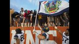 West Virginia players, from left-right, Trevon Wesco, Reese Donahue and Michael Brown celebrate with fans after defeating Texas during an NCAA college football game, Saturday, Nov. 3, 2018, in Austin, Texas. West Virginia won 42-41. (AP Photo/Michael Thomas)