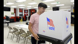 James Fitzgerald, of Boonsboro, Md., a poll worker for the last four months, sets up a voting booth at Northern Middle School in Hagerstown, Md., Monday, Nov. 5, 2018, on the eve of the 2018 midterm elections. (Colleen McGrath/The Herald-Mail via AP)