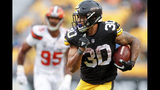 FILE - In this Sunday, Oct. 28, 2018, file photo, Pittsburgh Steelers running back James Conner (30) breaks away from Cleveland Browns defensive end Myles Garrett (95) for a touchdown in the second half of an NFL football game in Pittsburgh. Conner is thriving in Le'Veon Bell's absence. He's second in the league in total yards and is the first player in team history to have 10 total touchdowns through eight games. (AP Photo/Don Wright, File)