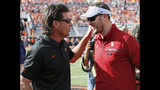 FILE - In this Saturday, Nov. 4, 2017, file photo, Oklahoma State head coach Mike Gundy, left, talks with Oklahoma head coach Lincoln Riley, right, before their NCAA college football game in Stillwater, Okla. While Oklahoma State has been erratic this season, and has been dominated in the rivalry series, the Cowboys have made it to overtime in two of their last three road games against Oklahoma. they won there in 2014, after an OT loss in 2012. (AP Photo/Sue Ogrocki, File)