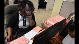 A Fulton County election worker counts provisional ballots, Wednesday, Nov. 7, 2018, in Atlanta. Malfunctioning voting machines, missing power cords, and hours-long lines at the polls are being scrutinized in Georgia, where the governor's race is still undecided as votes are still being tallied.(AP Photo/Mike Stewart)