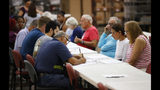 Employees at the Palm Beach County Supervisor of Elections office, left, duplicate damaged ballots under the watchful eyes of political observers, right, during a recount, Tuesday, Nov. 13, 2018, in West Palm Beach, Fla. (AP Photo/Wilfredo Lee)