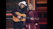 FILE - This Nov. 8, 2017 file photo shows hosts Brad Paisley, left, and Carrie Underwood during the opening of the 51st annual CMA Awards in Nashville, Tenn. Underwood will be working triple-duty at the 2018 Country Music Association Awards as co-host, performer and nominee. The singer, who is hosting the show alongside Brad Paisley for the 11th time, is pregnant and will hit the stage Wednesday night at the Bridgestone Arena in Nashville, Tennessee. (Photo by Chris Pizzello/Invision/AP, File)