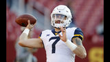 FILE - In this Saturday, Oct. 13, 2018 file photo, West Virginia quarterback Will Grier warms up before an NCAA college football game against Iowa State in Ames, Iowa. No. 6 West Virginia and No. 12 Oklahoma meet Friday night in Morgantown, W.Va., with the winner earning a berth in the Big 12 championship game next week. (AP Photo/Charlie Neibergall, File)