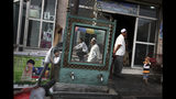 """FILE - In this Aug. 6, 2008, file photo, Uighurs are seen outside a restaurant in Kashgar in China's western Xinjiang province. More than a million Chinese civil servants have been assigned to move into the homes of Uighurs and other ethnic minorities, spending weeks as uninvited guests. While government notices about the """"Pair Up and Become Family"""" program portray it as an affectionate cultural exchange, exiled Uighurs living in Turkey said their loved ones saw the campaign as a chilling intrusion, aimed at coercing Uighurs into living secular lives like the Han majority. (AP Photo/Ng Han Guan, File)"""
