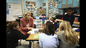 In this Nov. 26, 2018, photo, Secretary of Education Betsy DeVos chats with students at Cedar Grove Elementary to see how Hurricane Michael effected students and staff in Panama City, Fla. Since students in the Florida Panhandle county hardest hit by Hurricane Michael returned to classrooms within the past month, they've dealt with power outages, sporadic Internet, smaller enrollment, larger classes and schools sharing buildings. (Patti Blake/News Herald via AP)