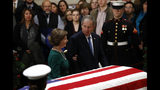 Former President George W. Bush glances toward former first lady Laura Bush as they pause in front of the flag-draped casket of former President George H.W. Bush as he lies in state in the Capitol Rotunda in Washington, Tuesday, Dec. 4, 2018. (AP Photo/Patrick Semansky)