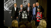 NHL commissioner Gary Bettman, center left, holds a jersey after the NHL Board of Governors announced Seattle as the league's 32nd franchise, Tuesday, Dec. 4, 2018, in Sea Island Ga.. Joining Bettman, from left to right, is Jerry Bruckheimer, David Bonderman, David Wright, Tod Leiweke and Washington Wild youth hockey player Jaina Goscinski. (AP Photo/Stephen B. Morton)
