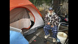 In this Tuesday, Dec. 4, 2018 photo, Steve Wilson poses for a photo next to the tent where he's been sleeping in the parking lot of an abandoned Toys R Us in Chico, Calif. Wilson, who was homeless in Chico before the worst wildfire in California history destroyed nearby Paradise, has seen the streets grow more crowded with homeless people. (AP Photo/Jonathan J. Cooper)