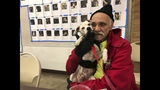 In this Tuesday, Dec. 4, 2018 photo, Bob Talk cuddles his dog, Princeton, at a Red Cross disaster shelter in Chico, Calif. Talk had lived in his trailer for three days when fire swept through the town of Paradise and destroyed his home last month, making him homeless again. The future is uncertain for all of the fire's victims, but it's uniquely challenging for the many like Talk who were already living on the edge, homeless or nearly so, before escaping with their lives and little else. (AP Photo/Jonathan J. Cooper)