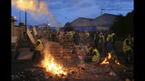 """FILE - In this Tuesday, Dec. 5, 2018 file photo, demonstrators stand at a makeshift barricade set up by the """"yellow jackets"""" protesters to block the entrance of a fuel depot in Le Mans, western France. Even proponents of carbon taxes acknowledge that an increase in fuel taxes can disproportionally hurt low-income people. Energy costs make up a larger portion of their overall expenses, so a fuel price increase eats up more of their paycheck and leaves with less to spend. (AP Photo/David Vincent)"""