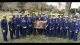 In this Dec. 5, 2018 photo, U.S. Coast Guard members past and present from around the country stand around a photograph of Olivia Hooker during her funeral service held in White Plains, N.Y. Hooker, the first African-American woman to serve in the U.S. Coast Guard and one of the last survivors of a race riot in Oklahoma, has been laid to rest with military honors. Hooker passed away on Nov. 21, 2018, at the age of 103. (Petty Officer 3rd Class Steve Strohmaier/U.S. Coast Guard via AP)