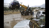 A forklift removes destroyed cars after heavy rain caused flash floods near Kerynia city in the Turkish Cypriots breakaway north part of Cyprus, Thursday, Dec. 6, 2018. Police in the breakaway north of ethnically split Cyprus say the bodies of three people have been recovered from river beds at two different locations after flash floods are believed to have swept them away. (AP Photo/Petros Karadjias)