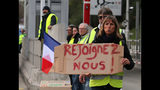 """A demonstrator holds a placard reading """" Join us"""" as they stand by toll gates on a motorway at Biarritz southwestern France, Wednesday, Dec.5, 2018. The concessions made by French president Emmanuel Macron's government in a bid to stop the huge and violent anti-government demonstrations seemed on Wednesday to have failed to convince protesters, with trade unions and disgruntled farmers now threatening to join the fray. (AP Photo/Bob Edme)"""