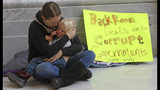 Letesha Case holds her daughter Aurora Case, 2, as they sit next to their sign Monday Dec. 3, 2018, at the Utah state Capitol in Salt Lake City. Lawmakers in conservative Utah passed sweeping changes Monday to a new voter-approved medical-marijuana ballot measure under a planned compromise that secured the support of the influential Mormon church but sparked a backlash from advocates. (AP Photo/Rick Bowmer)
