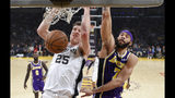 San Antonio Spurs center Jakob Poeltl, left, of Austria, dunks as Los Angeles Lakers center JaVale McGee defends during the first half of an NBA basketball game Wednesday, Dec. 5, 2018, in Los Angeles. (AP Photo/Mark J. Terrill)