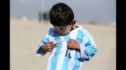 FILE - In this Friday, Feb. 26, 2016 file photo, five-year-old Afghan Lionel Messi fan Murtaza Ahmadi poses for photograph, as he wears a shirt signed by Messi, in Kabul, Afghanistan. A young Afghan soccer fan who shot to fame after he was photographed in a Messi shirt made from a plastic bag has been forced to flee with his family to the Afghan capital after criminal gangs and the Taliban threatened to kill or kidnap him. Shafiqa Ahmedi said Friday, Dec. 7, 2018 that criminals threatened to kidnap her now-7-year-old son Murtaza, a fan of Argentinian soccer star Lionel Messi, after demanding money. (AP Photo/Rahmat Gul, file)