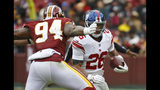 New York Giants running back Saquon Barkley (26) tries to get past Washington Redskins outside linebacker Preston Smith (94) during the first half of an NFL football game Sunday, Dec. 9, 2018, in Landover, Md. (AP Photo/Patrick Semansky)