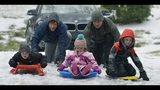 In this Dec. 9, 2018 photo, Dan Weber and Alex McCoy push sledders, from left, sledders Jack Weber, Allie McCoy and Hudson McCoy in the Freedom Park area in Charlotte, N.C. (Diedra Laird/The Charlotte Observer via AP)