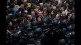 FILE - In this Oct. 1, 2017 file photo, Spanish national police block people trying to reach a voting site at a school assigned to be a polling station by the Catalan government for a secession referendum in Barcelona, Spain. Spain's central government threatened on Tuesday, Dec. 11, 2018, to send in national police to ensure security in Catalonia if regional authorities fail to stop recent disruptions by pro-independence protesters on major highways. (AP Photo/Emilio Morenatti, File)