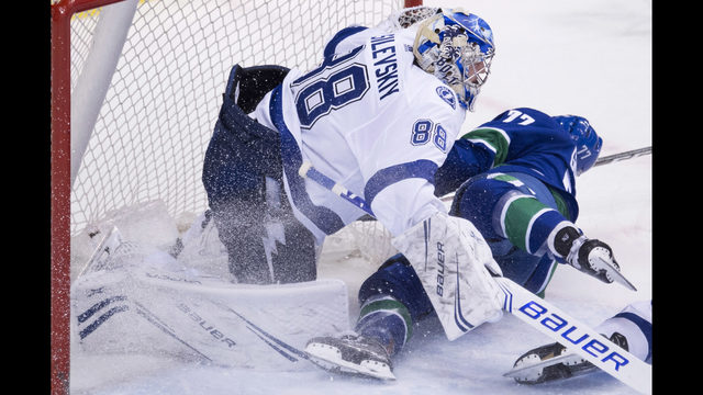 Vancouver Canucks right wing Nikolay Goldobin (77) crashes into Tampa Bay  Lightning goaltender Andrei Vasilevskiy (88) during the third period of an  NHL ... 19ea6865d