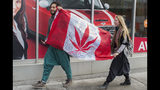 FILE - In this Oct. 17, 2018, file photo, people hold up a Canadian flag with a marijuana logo on it outside a government cannabis store in Montreal. California became America's largest legal marketplace in 2018, while Canada became the second and largest country with nationwide legal recreational marijuana. (Graham Hughes/The Canadian Press via AP, File)