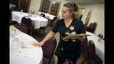 In this Tuesday, Dec. 18, 2018 photo, Shawna Green, waitress at Granny Shaffer's, puts out menus for customers at the restaurant in Joplin, Mo. Wages will be increasing for millions of low-income workers across the U.S. as the new year ushers in new laws in numerous states. In Missouri and Arkansas, minimum wages are rising as a result of voter-approved ballot initiatives. (Roger Nomer/The Joplin Globe via AP)