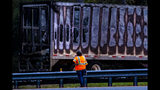 CORRECTS SOURCE TO THE GAINESVILLE SUN A worker looks at a charred semi-truck after a wreck with multiple fatalities on Interstate 75, south of Alachua, near Gainesville, Fa., Thursday, Jan. 3, 2019. Two big rigs and two passenger vehicles collided and spilled diesel fuel across the Florida highway Thursday, sparking a massive fire that killed several people, authorities said. (Lauren Bacho/The Gainesville Sun via AP)