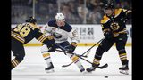 Buffalo Sabres' C.J. Smith (49) battles Boston Bruins' Matt Grzelcyk (48) and David Backes (42) for the puck during the first period of an NHL hockey game in Boston, Saturday, Jan. 5, 2019. (AP Photo/Michael Dwyer)