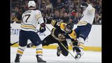 Boston Bruins' Sean Kuraly (52) falls while battling Buffalo Sabres' Remi Elie, right, for the puck during the second period of an NHL hockey game in Boston, Saturday, Jan. 5, 2019. (AP Photo/Michael Dwyer)