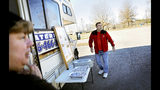"Sabine, left, and Jeff Cool watch as fellow food trucks pull into a lot all vying for a smaller-than-normal lunch crowd outside a NASA complex in Huntsville, Ala., Wednesday, Jan. 9, 2019. Today, people and businesses which rely on that federal largesse for their livelihood are showing the strain of a government shutdown. ""It kind of hurt a little bit; we're just rolling with the punches,"" Jeff Cool said. (AP Photo/David Goldman)"