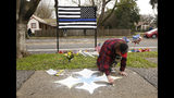 Matthew Ottele draws a star on the sidewalk Friday, Jan. 11, 2019, near the scene were Davis Police Officer Natalie Corona was shot and killed in Davis, Calif. Corona, 22, who had been on the job only a few weeks was slain, Thursday, by a suspect who opened fire as she was investigating a three-car crash. The suspect was later found dead from a self-inflicted gunshot, following a standoff with officers. (AP Photo/Rich Pedroncelli)