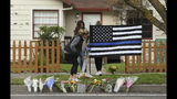 Sydney Carlier, foreground, accompanied by roommates, Jenna Brouwer, center and Camille Foder, behind flag, places flowers on a memorial for slain Davis Police Officer Natalie Corona, Friday, Jan. 11, 2019, in Davis, Calif. Corona, 22, who had been on the job only a few weeks, was shot and killed, Thursday, by a suspect who opened fire as she was investigating a three-car crash. The suspect was later found dead from a self-inflicted gunshot, following a standoff with officers. (AP Photo/Rich Pedroncelli)