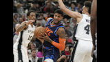 Oklahoma City Thunder's Paul George, center, drives between San Antonio Spurs' Derrick White, right, and DeMar DeRozan during the first half of an NBA basketball game, Thursday, Jan. 10, 2019, in San Antonio. (AP Photo/Darren Abate)
