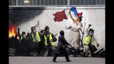 "A woman passes by a mural by street artist PBOY depicting Yellow Vest (gilets jaunes) protestors inspired by a painting by Eugene Delacroix, ""La Liberte guidant le Peuple"" (Liberty Leading the People), in Paris, Thursday, Jan. 10, 2019. French President Emmanuel Macron is facing a mountain of challenges in the new year starting with yellow vest protesters who are back in the streets to show their anger against high taxes and his pro-business policies that they see as favoring the wealthy rather than the working class. (AP Photo/Christophe Ena)"