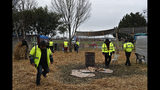 Protestors wearing yellow vests stand in a makeshift camp on a roundabout near Senlis, north of Paris, Thursday, Jan. 10, 2019. With its makeshift grocery, camp beds and community spirit, the large central island about 60 kilometers north of Paris has been transformed over the past two months into an encampment where dozens of yellow vests protesters gather day in day out to organize their long-standing fight against the French government. (AP Photo/Thibault Camus)