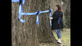 Vicky Oliverius ties blue ribbons on trees, Friday, Jan. 11, 2019, near the scene were Davis Police Officer Natalie Corona was shot and killed in Davis, Calif. Corona, 22, who had been on the job only a few weeks was slain, Thursday, by a suspect who opened fire as she was investigating a three-car crash. The suspect was later found dead from a self-inflicted gunshot, following a standoff with officers. (AP Photo/Rich Pedroncelli)
